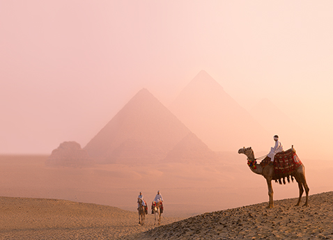 Three camels and riders at the pyramids in Giza, Egypt